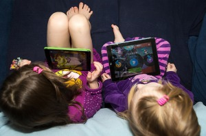 Two little girls sit with tablets on their laps. The photo is taken above their heads looking down on them.