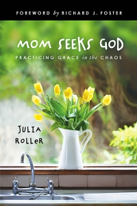 "Front cover of Julia Roller's book ""Mom Seeks God."" Soft focus garden in the background; white jug-vase with yellow flowers in it in the center."